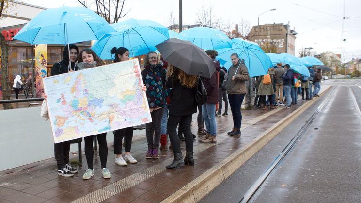Junge Leute mit einer Europakarte und Europa-Regenschirmen stehen auf dem Bahnsteig