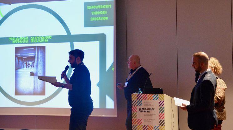 Mann mit Mikrofon in der Hand erläutert die Ergebnisse des Projekts OVERHOPE
