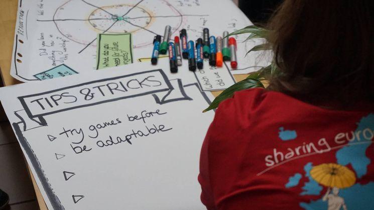 """Plakat mit der Überschrift """"Tips and Tricks"""". Davor sitzt eine Frau im EuroPeer-T-Shirt mit der Aufschrift """"Sharing Europe"""""""