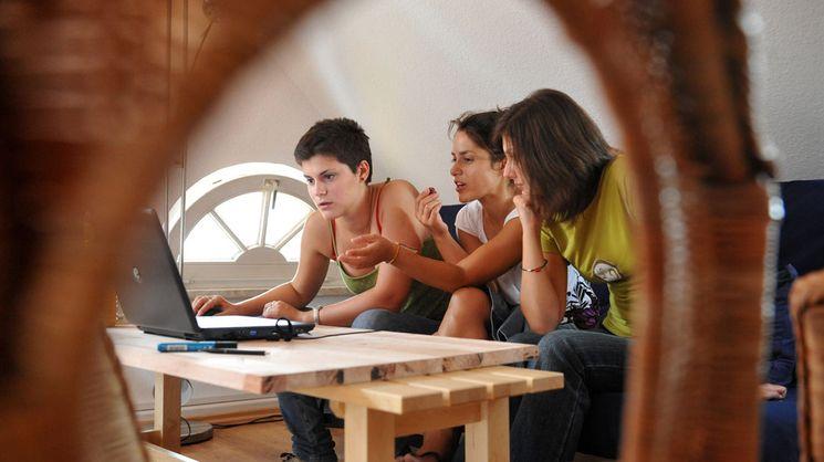 Gruppe junger Menschen vor einem Laptop