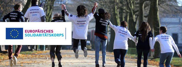 Junge Leute gehen Hand in Hand einen Straße entlang und tragen T-Shirts mit der Aufschrift Europäisches Solidaritätskorps