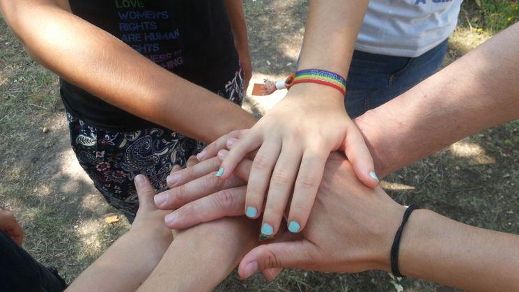 Sechs Jugendliche legen ihre Hände aufeinander. Eine junge Frau trägt ein Armband mit der Aufschrift PRIDE / Quelle: ©wir weit weg/KINDERVEREINIGUNG Leipzig e.V.