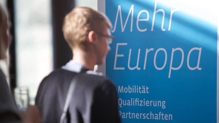 """Ein junger Mann steht vor einem Banner mit der Aufschrift """"Mehr Europa"""""""