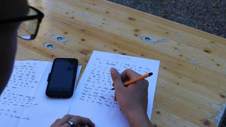 Ein Teilnehmer schreibt seine Gedanken zum Thema Freiheit auf ein Blatt Papier