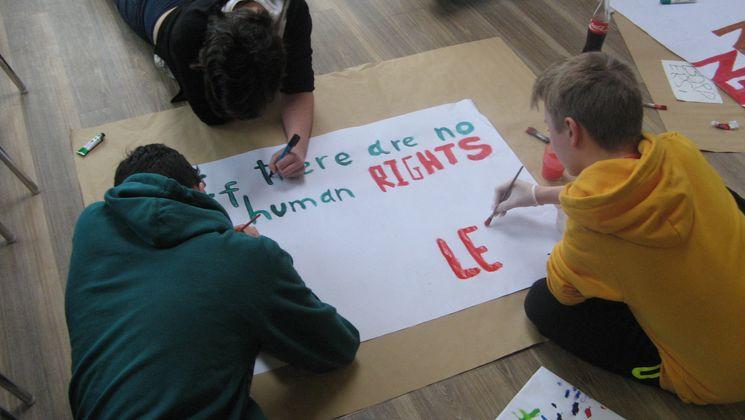 Teilnehmer eine Jugendbegegnung malen ein Plakat zum Thema Menschenrechte