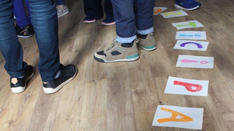 Füße der Teilnehmenden und daneben liegen Buchstaben, die das Wort Participation bilden