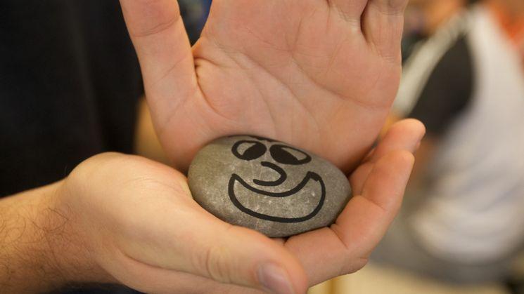 Person hält einen flachen Stein in der Hand, auf den ein lachendes Gesicht gemalt ist