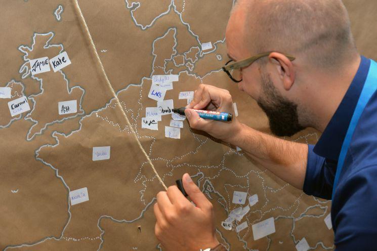 Mann vor einer Moederationswand, auf der die Umrisse Europas abgebildet sind