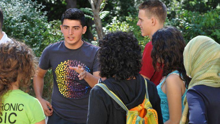 Eine Grupope junger Menschen steht zusammen und diskutiert