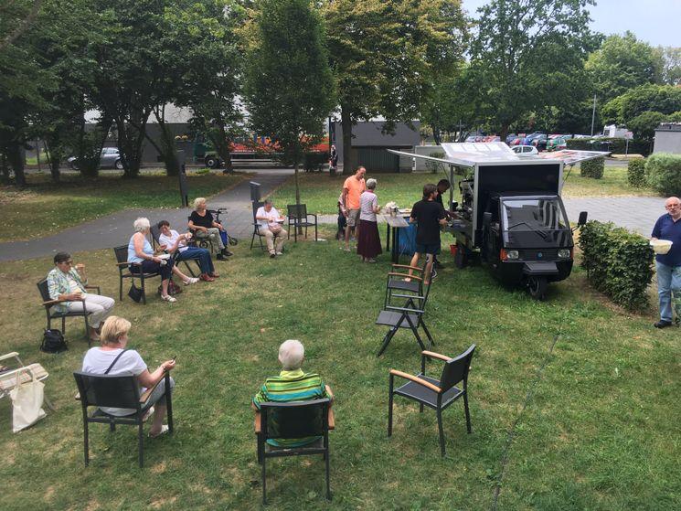 Kaffeemobil mit Menschen auf Stühlen, die im Kreis sitzen